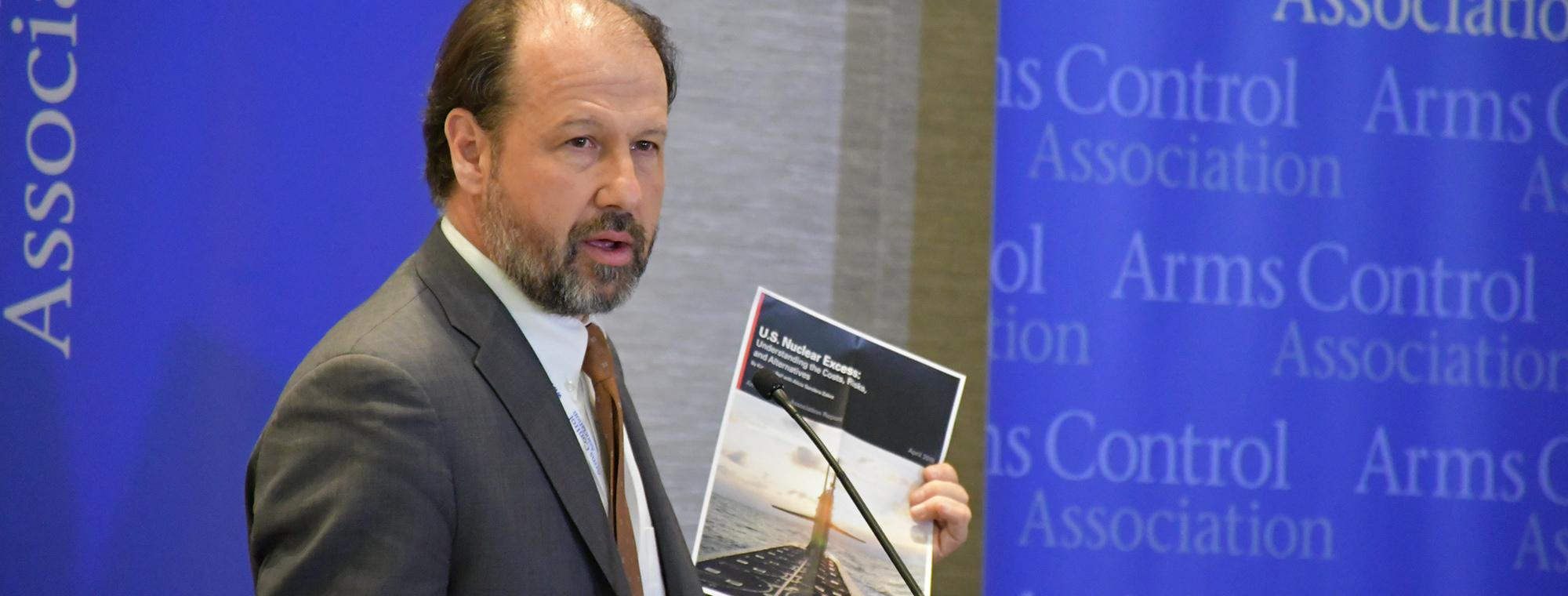 A man at a podium with a new report at an ACA event