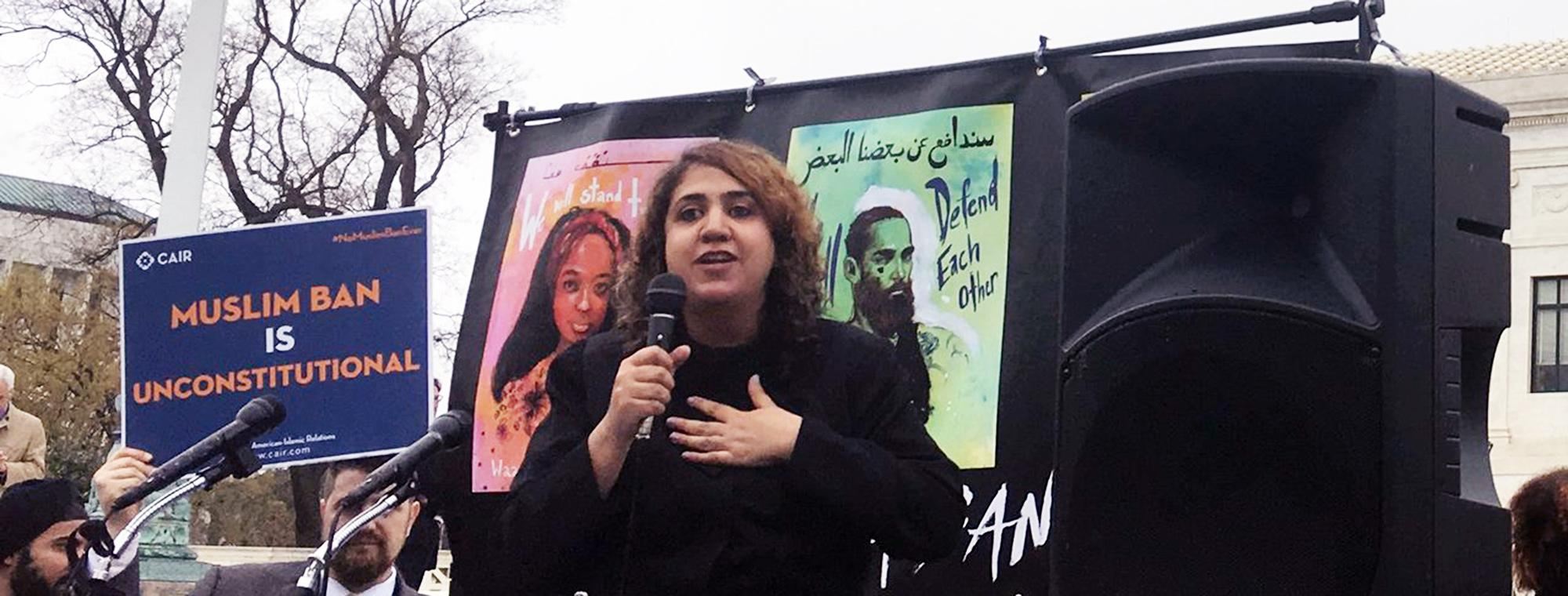 a woman speaking at a rallyl