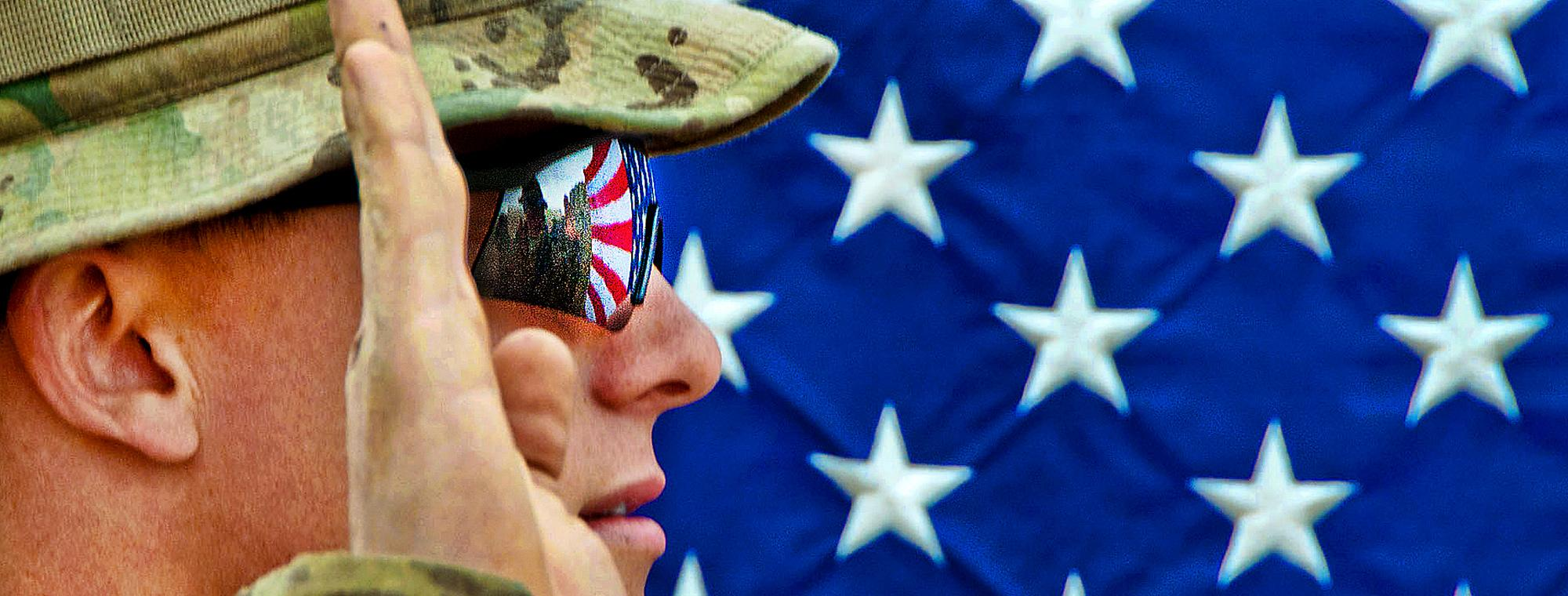 The American flag reflects in the glasses of an U.S. Army officer as he reenlists as a paratrooper on Combat Outpost Qara Baugh in Afghanistan's Ghazni province, April 22, 2012. The soldier is assigned to the 82nd Airborne Division's 1st Brigade Combat Te